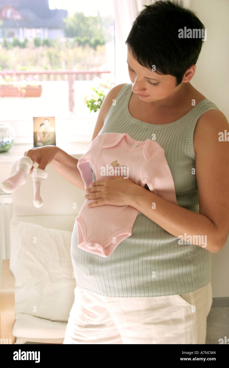 661d0a7513052 indoor flat room sittingroom woman young 25 30 brunette shirt stomach pregnancy  pregnant stand hold sock socks baby crowler t