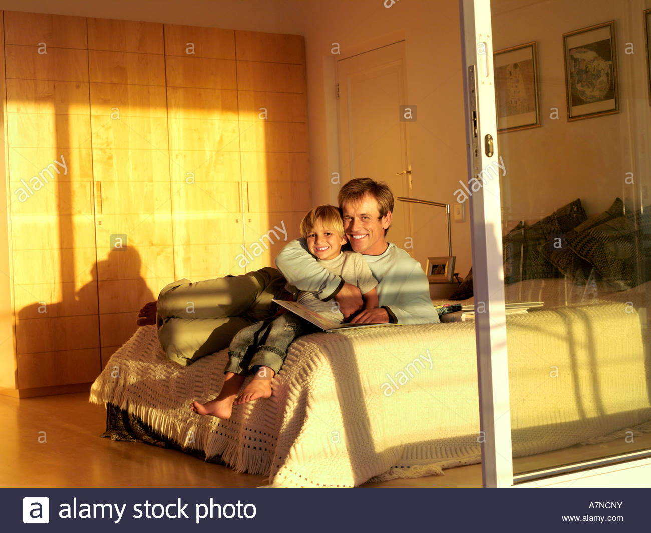 Father and son 5 7 sitting on bed with photo album smiling portrait view through sliding doors - Stock Image
