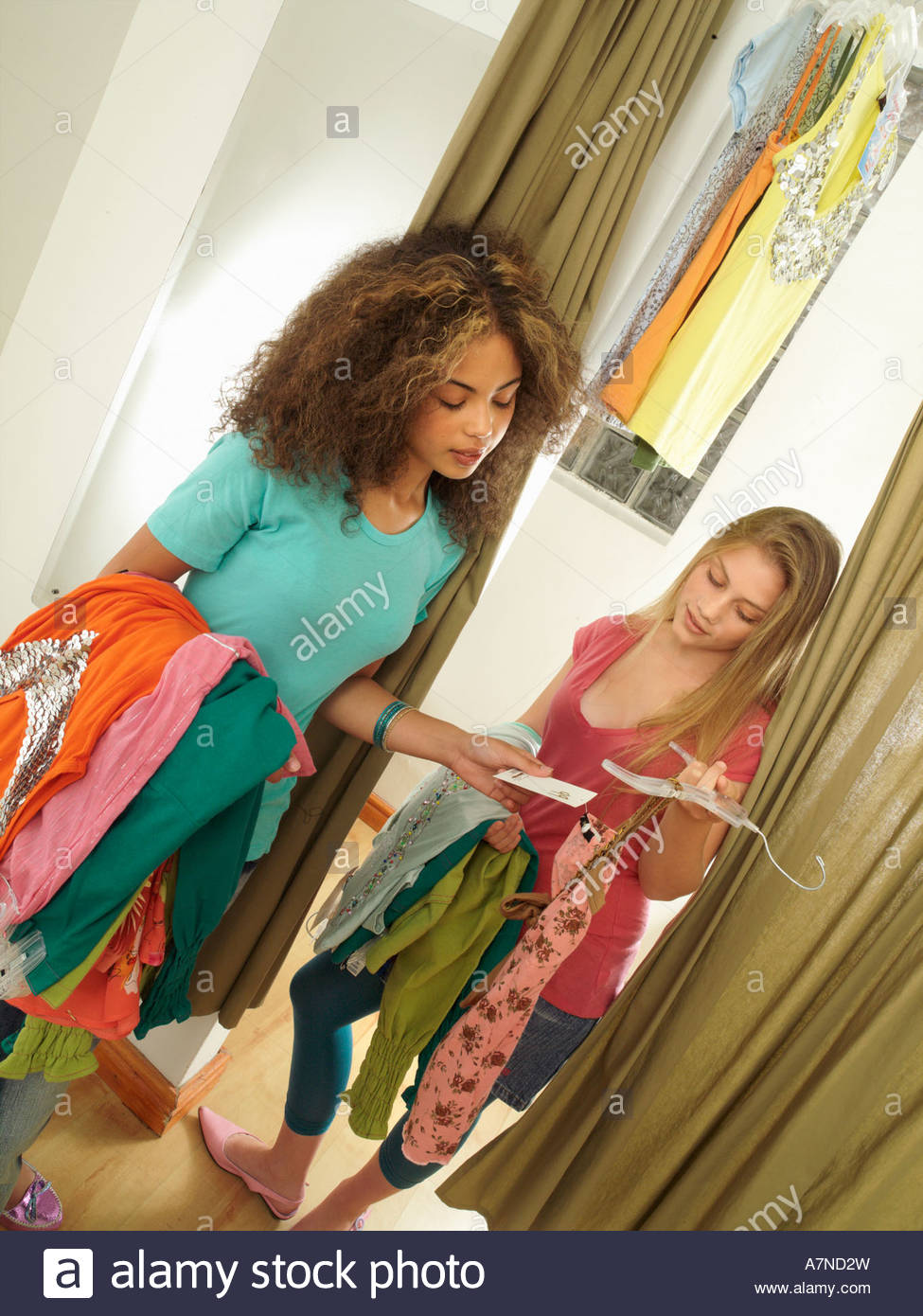 Two teenage girls 15 17 standing in clothes shop fitting room checking new top price tag tilt - Stock Image