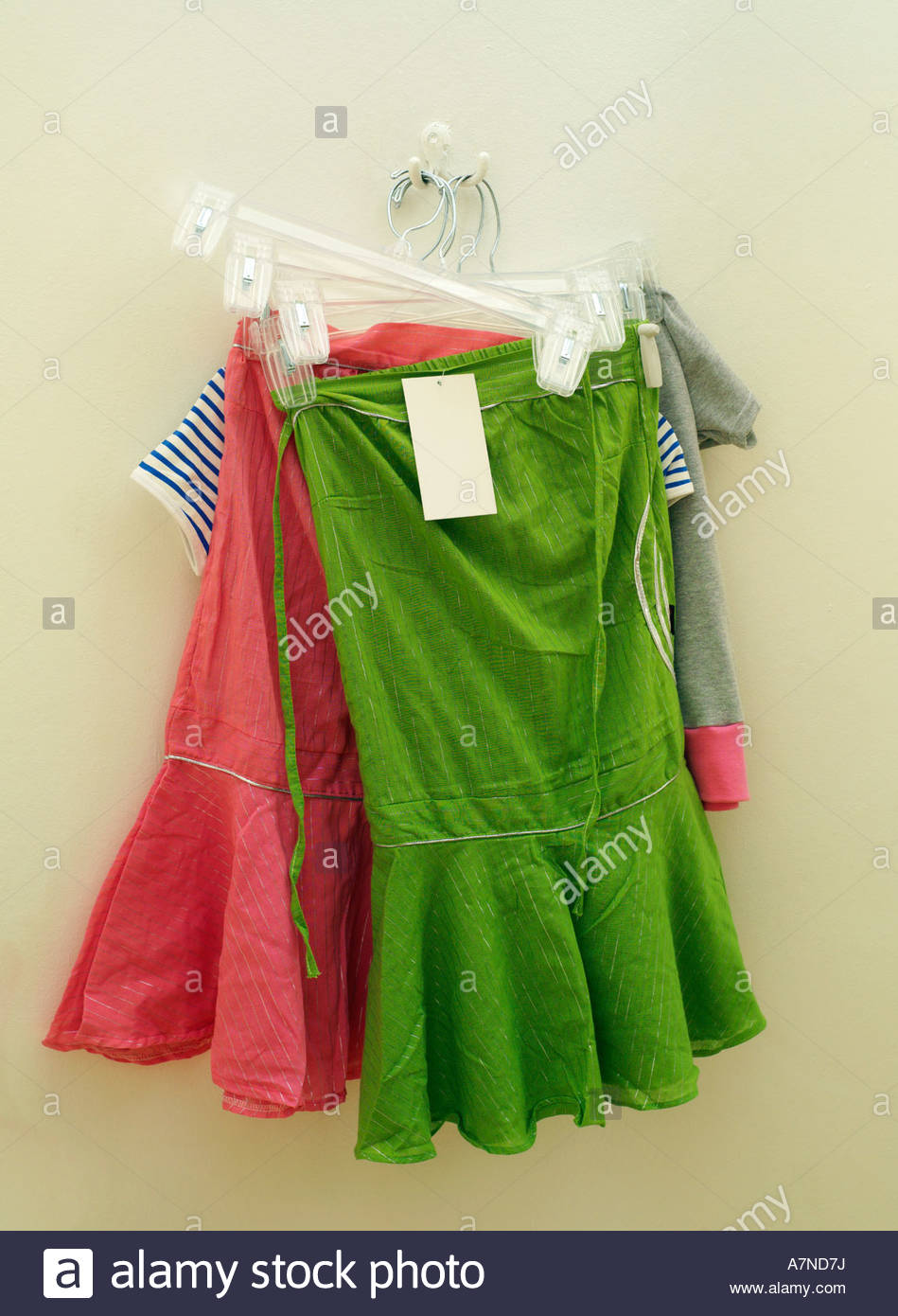 New green and pink skirts hanging on coathanger price tag attached close up - Stock Image