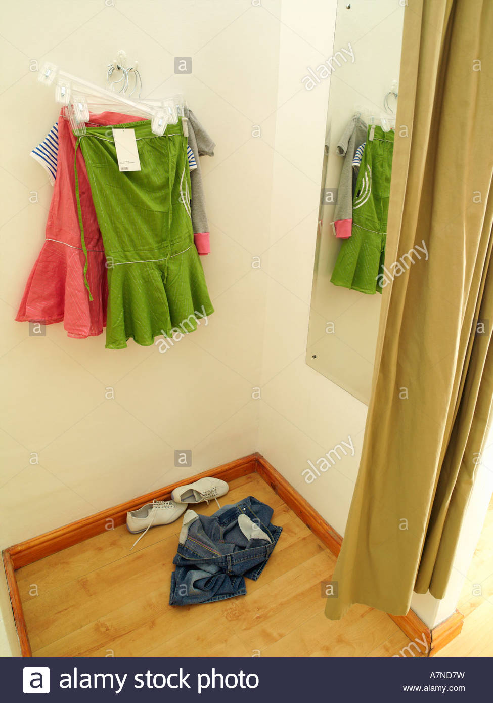 New green and pink skirts hanging on coathanger in clothes shop fitting room reflection in mirror - Stock Image