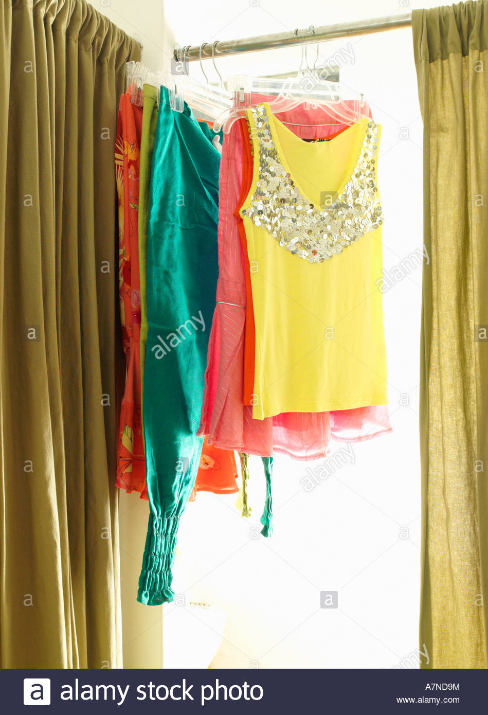 Colourful new clothes hanging from rail in clothes shop fitting room - Stock Image