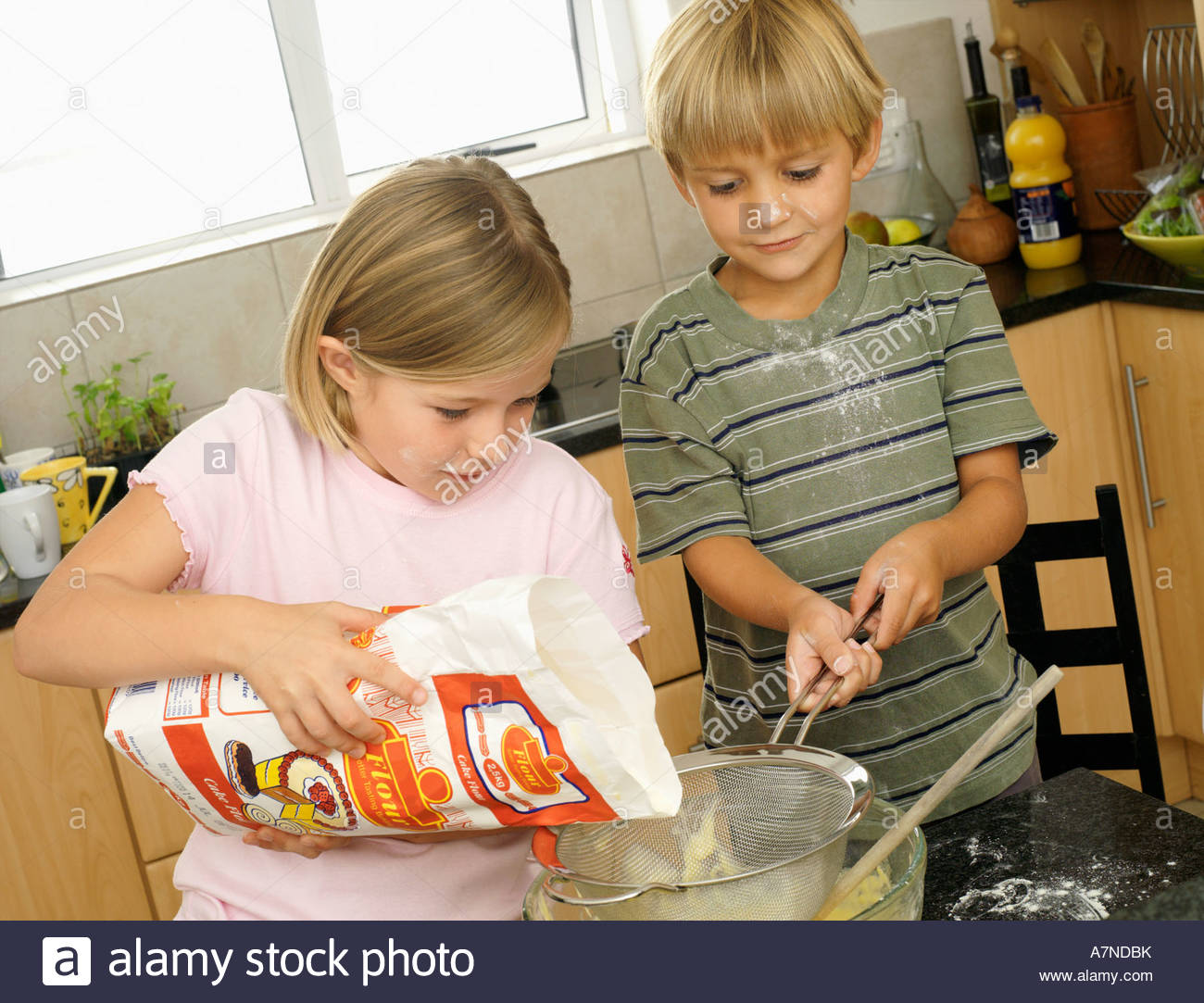 Boy 5 7 and girl 6 8 making cake mix in kitchen girl pouring flour into glass bowl tilt - Stock Image