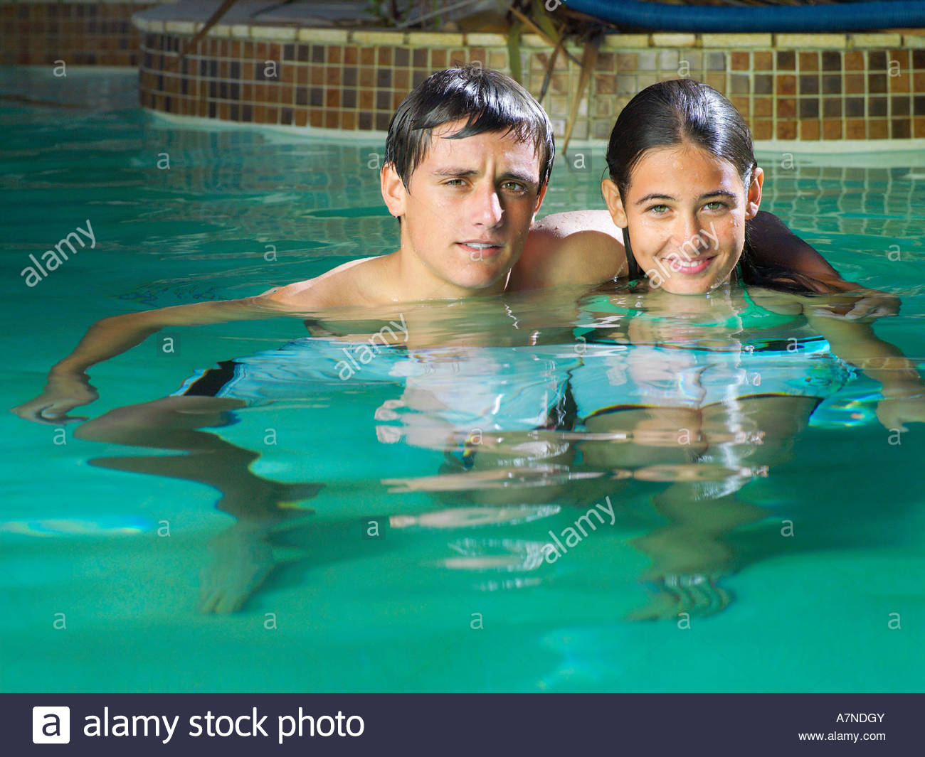 Teenage couple 15 17 relaxing in swimming pool boy with arm around girl smiling portrait Stock Photo