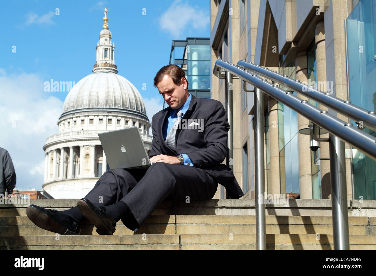 London England United Kingdom UK City gent using laptop computer in shadow of St Pauls Cathedral - Stock Image