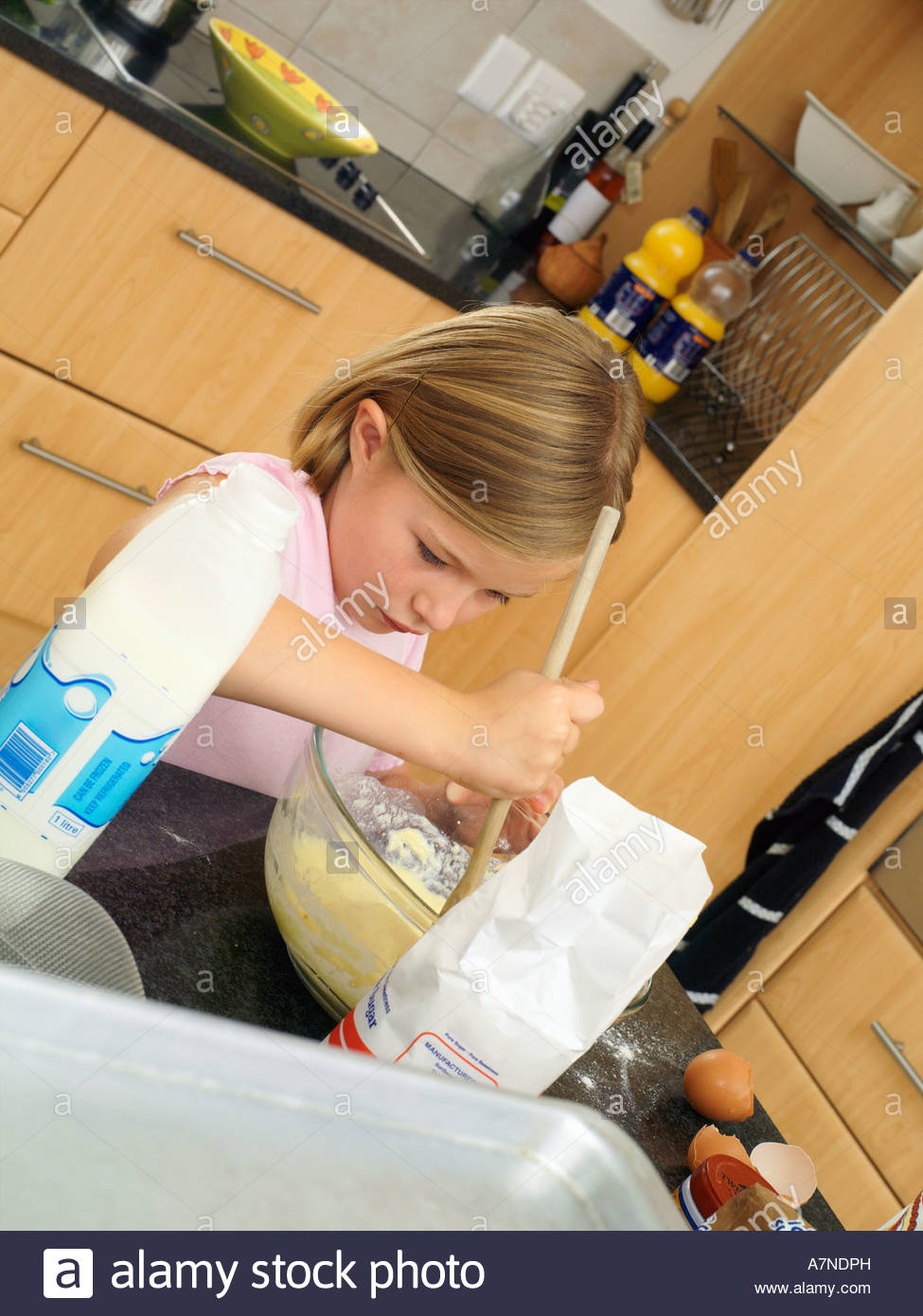 Girl 6 8 standing in kitchen mixing flour eggs and milk in glass bowl with wooden spoon tilt - Stock Image