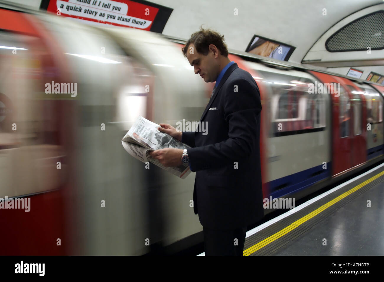 City gent reading newspaper on London Underground station with train approaching England United Kingdom Stock Photo