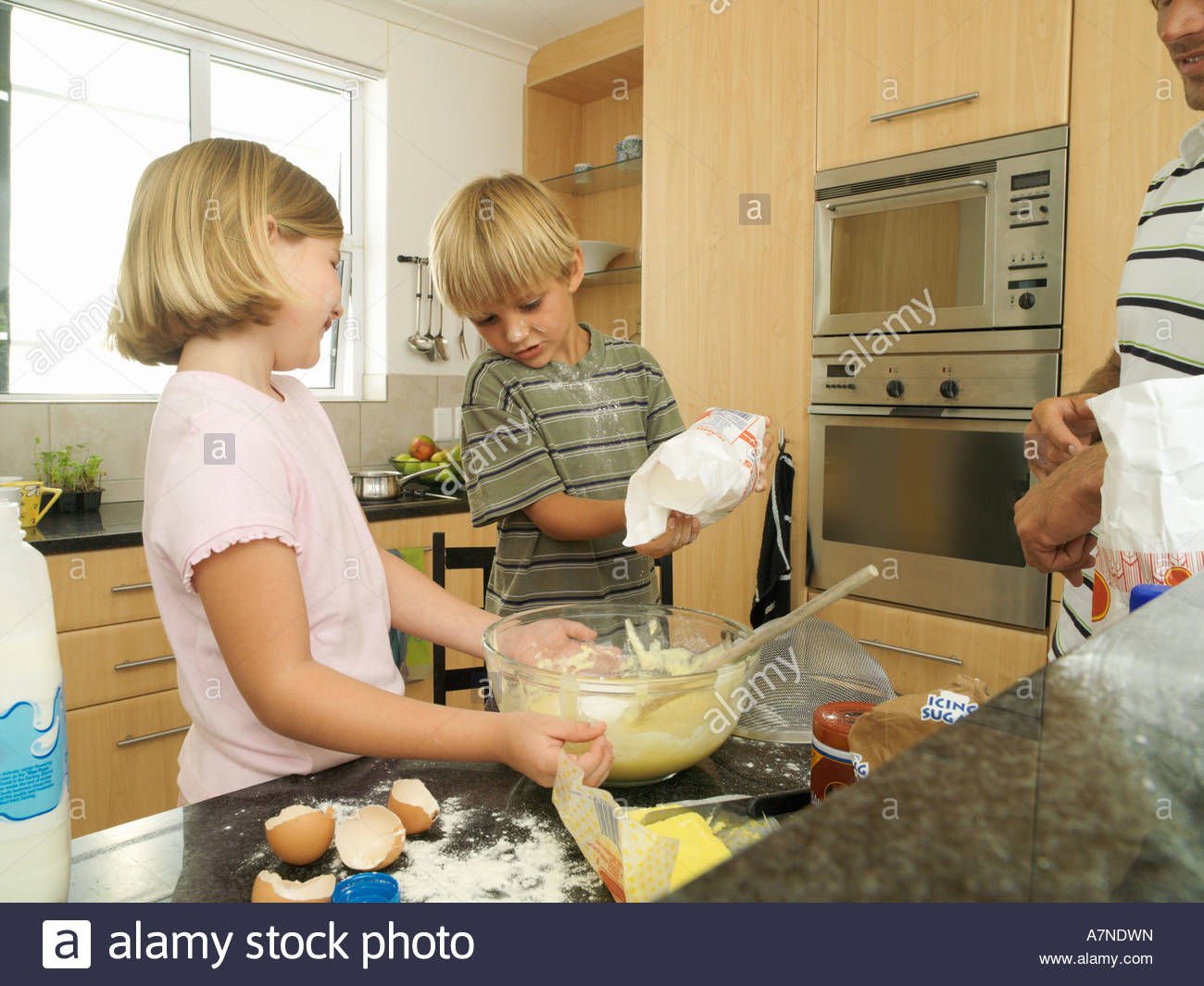 Boy 5 7 and girl 6 8 making cake mix in kitchen boy pouring flour into bowl father watching - Stock Image