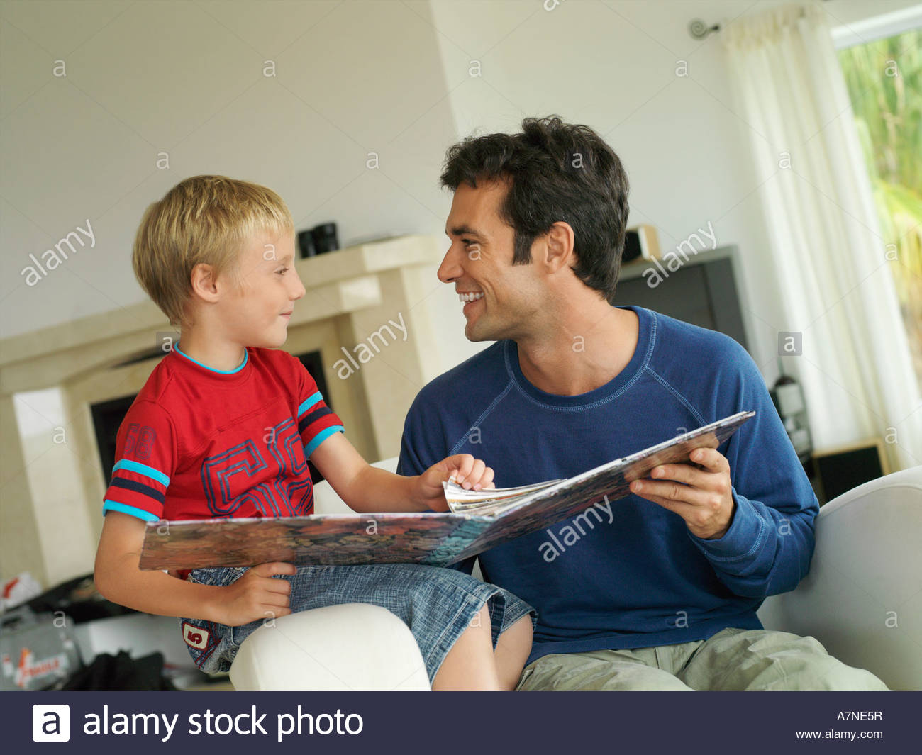 Father and son 5 7 looking at photo album at home sitting in chair face to face smiling tilt - Stock Image