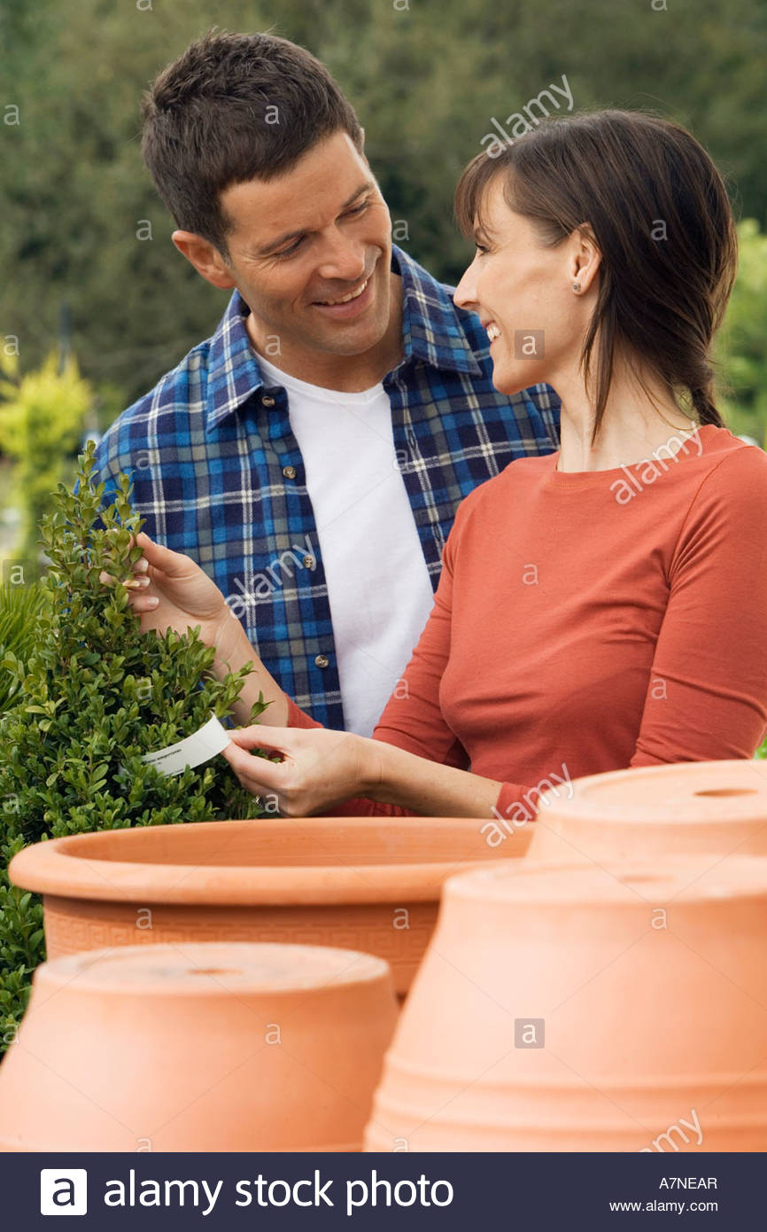 Couple shopping for plant pots in garden centre woman holding price tag smiling - Stock Image