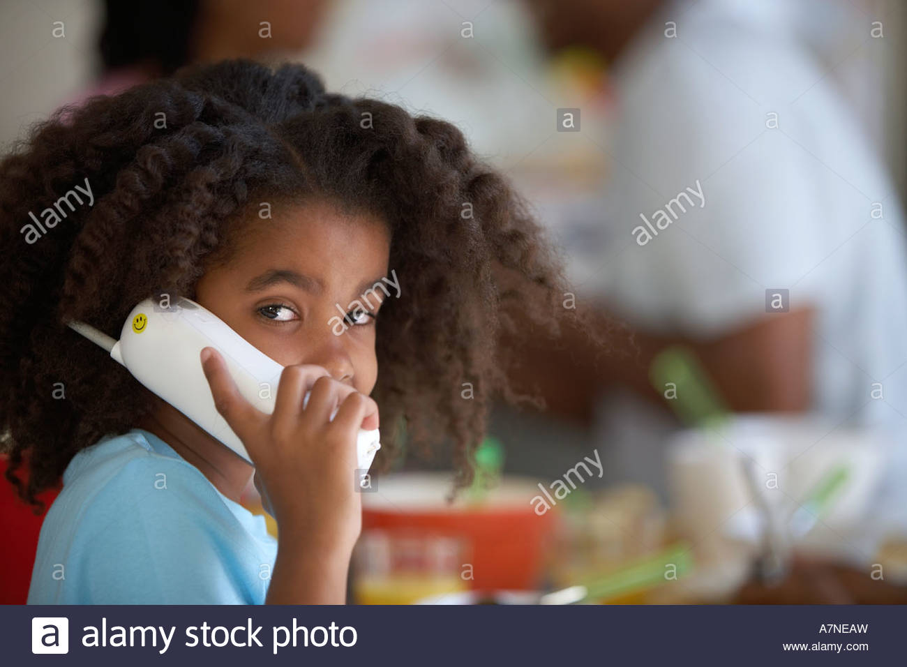 Girl 7 9 sitting at kitchen table using cordless phone portrait parents in background - Stock Image