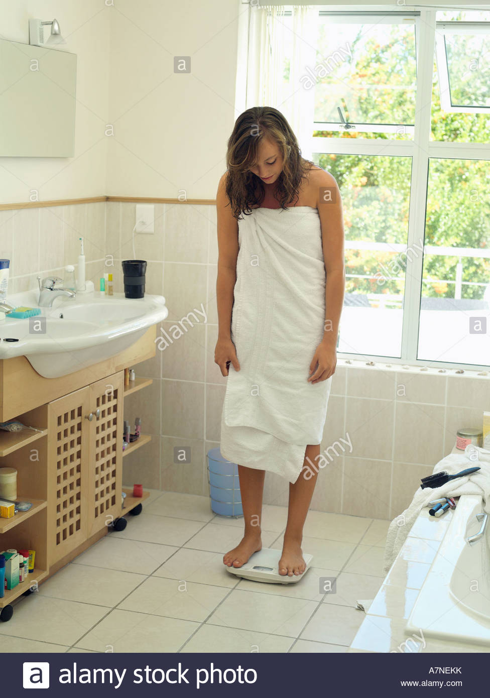 Teenage girl 15 17 standing on bathroom weighing scales wrapped in white  towel smiling - Stock fd2c6a924
