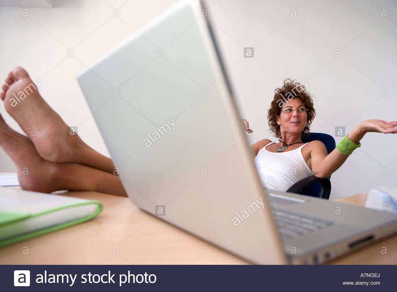 Businesswoman shrugging shoulders resting bare feet up on desk in office laptop in foreground - Stock Image