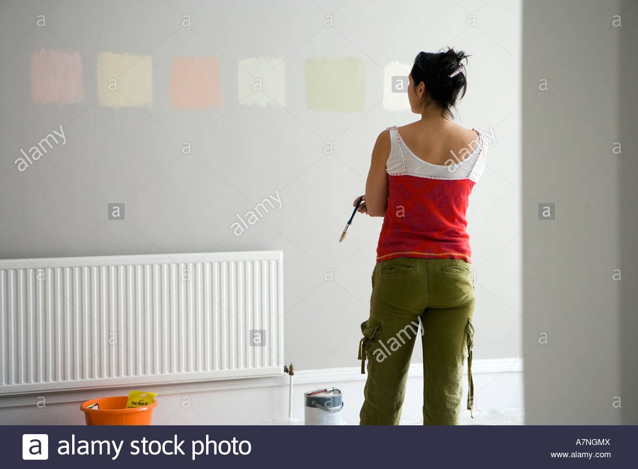 Woman Looking At Various Paint Colours On Wall In Undecorated Room Making Decision Rear View