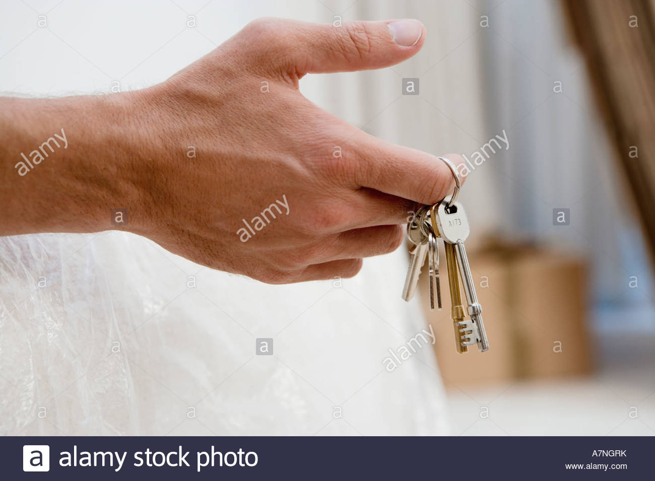 Man holding set of keys close up of hand side view - Stock Image
