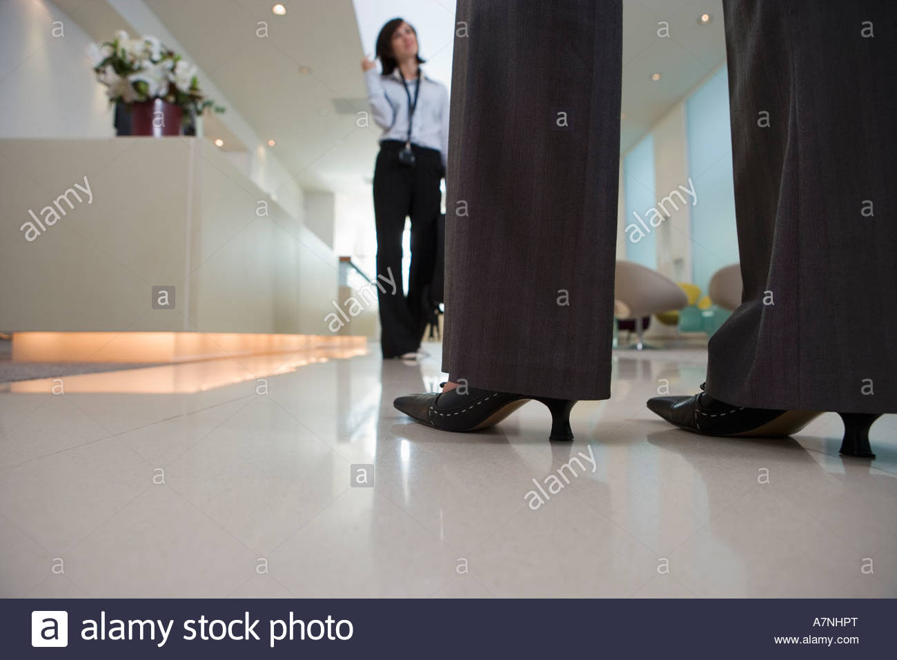 Two businesswomen talking in lobby low section surface level focus on legs and high heels in foreground - Stock Image