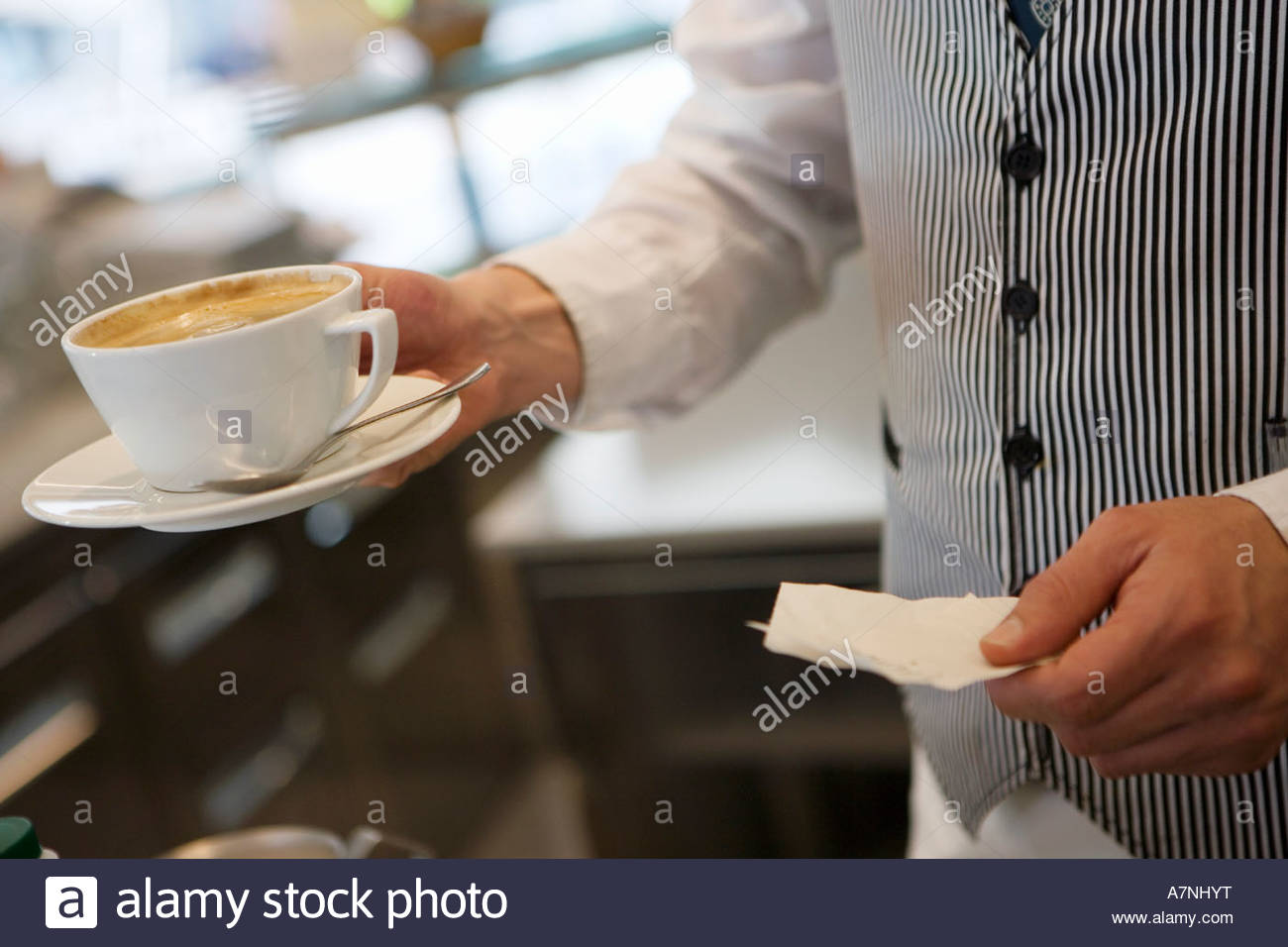 Waiter serving cup of coffee in cafe holding check receipt side view mid section close up - Stock Image