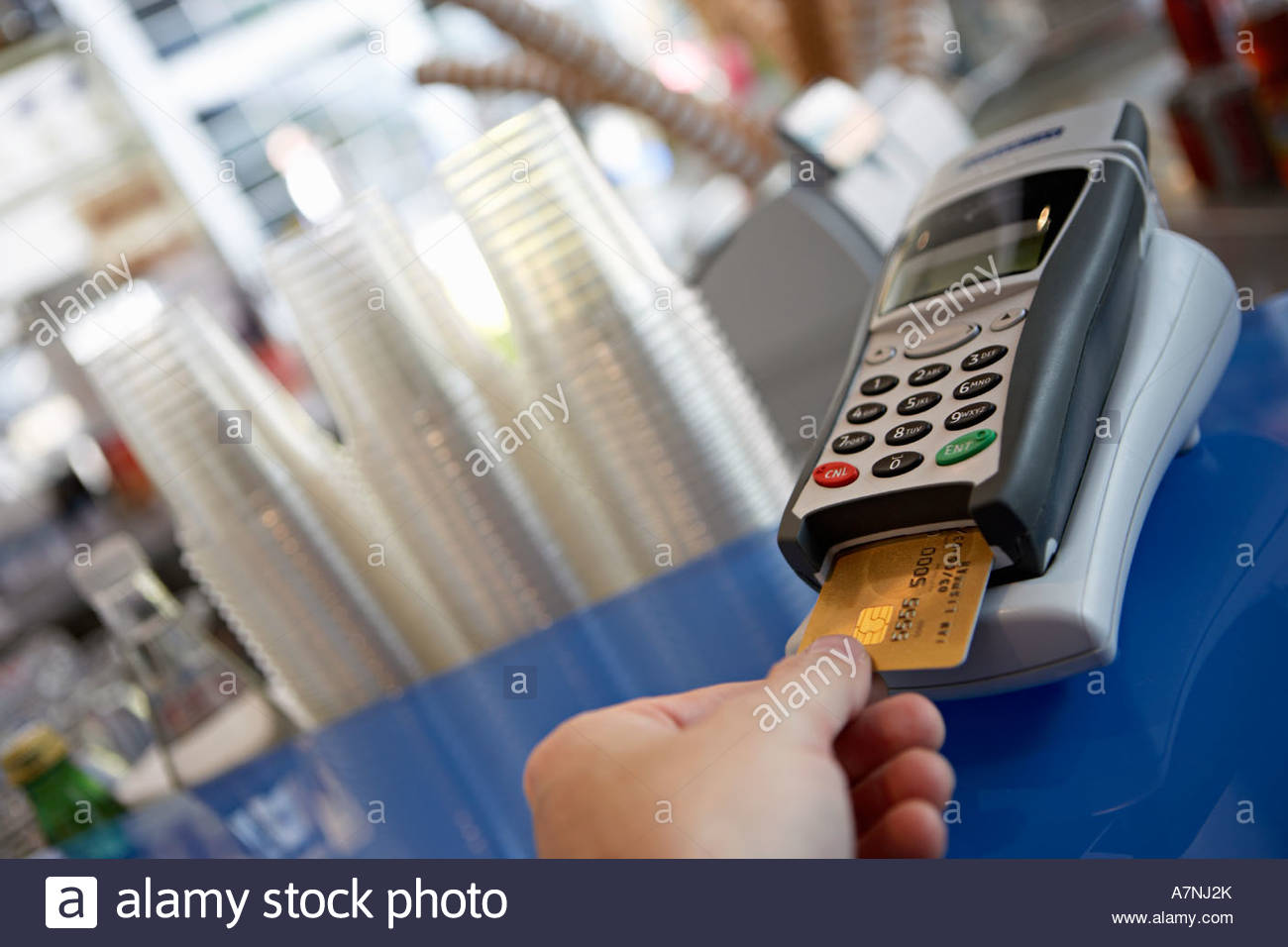 Customer placing bank card in credit card reader close up rear view personal perspective tilt - Stock Image