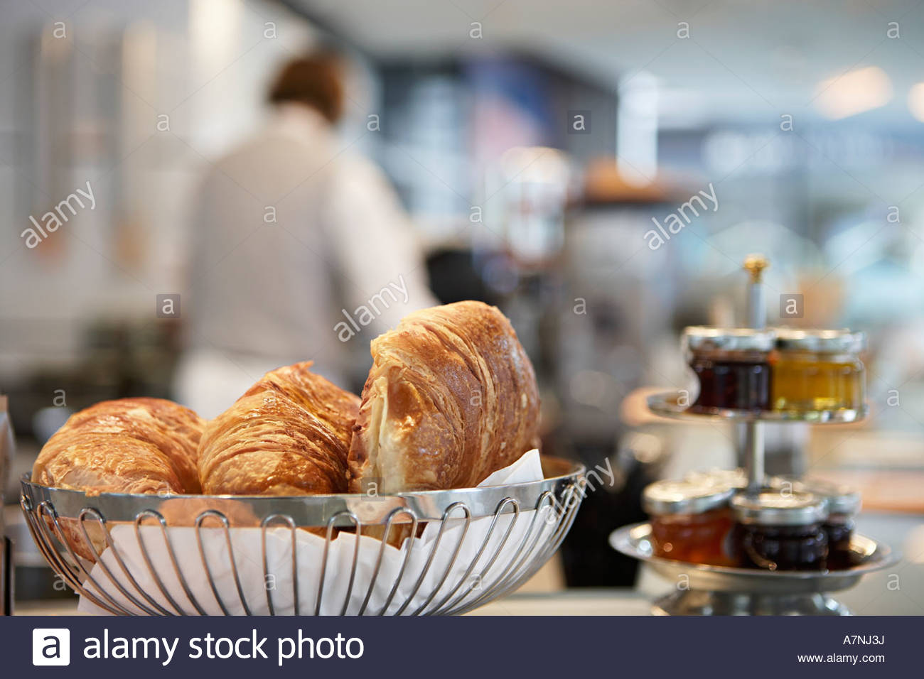 Croissants and assortment of preserves in cafe close up waiter in background focus on foreground - Stock Image