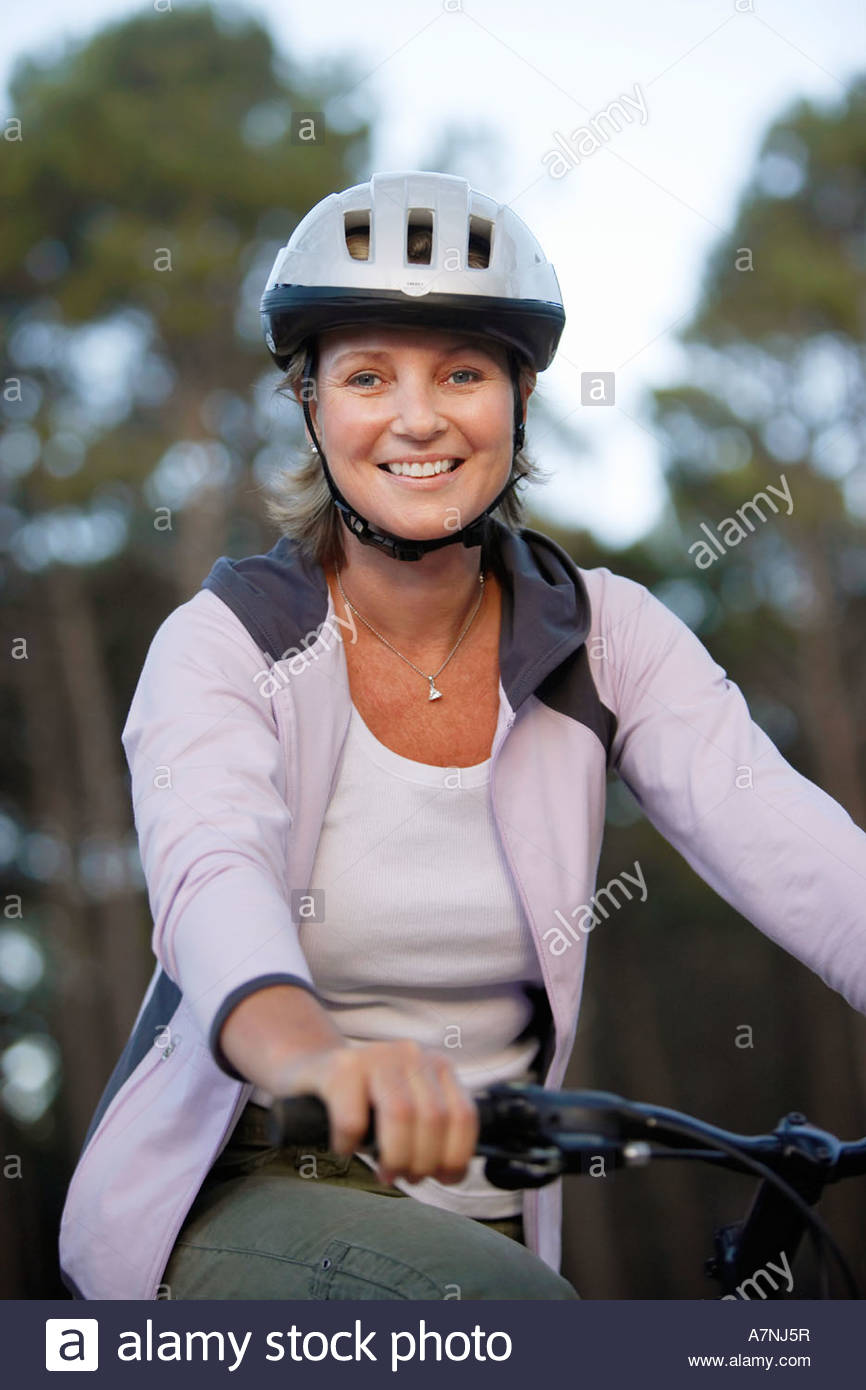 Woman wearing cycling helmet and pink hooded sports top sitting on bicycle smiling portrait Stock Photo