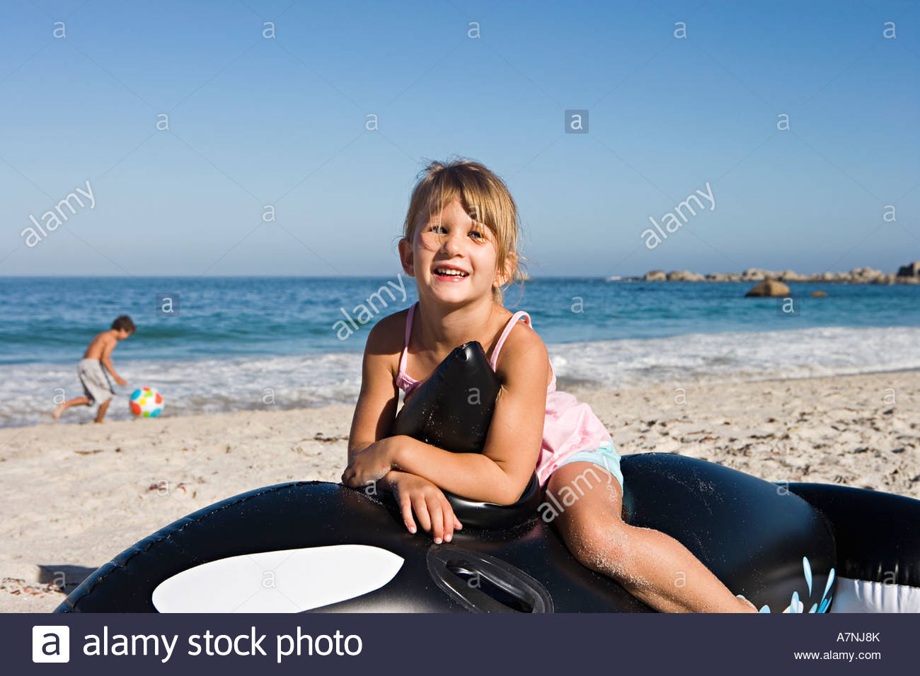 Girl 5 7 sitting on inflatable toy whale on sandy beach smiling portrait - Stock Image