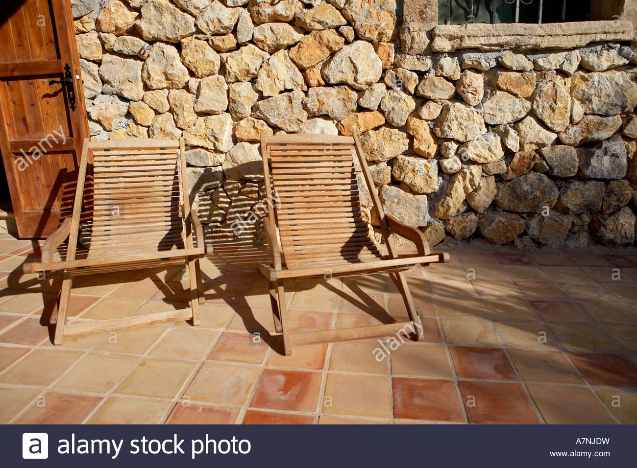 Two wooden deckchairs on tiled patio stone wall in background - Stock Image