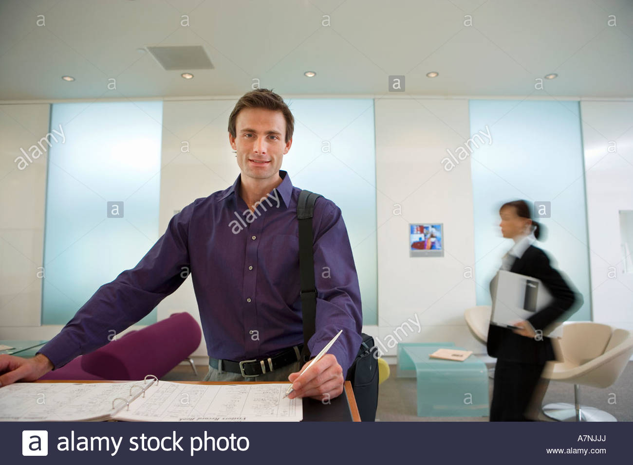 Businessman signing guestbook in reception area smiling portrait businesswoman in background focus on foreground - Stock Image
