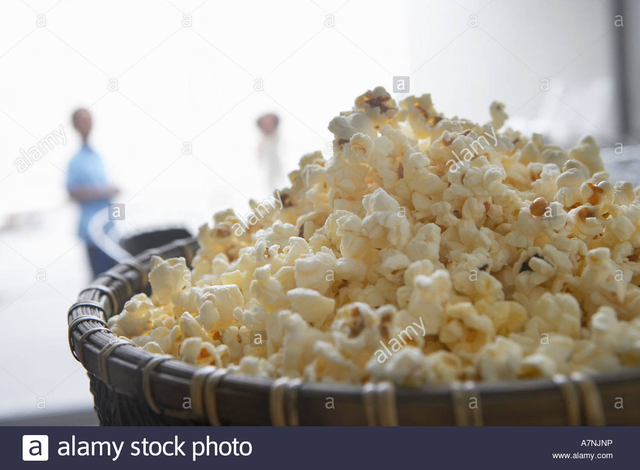 Bowl of popcorn close up people in background focus on foreground - Stock Image
