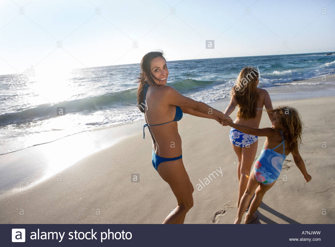 Two girls 5 12 wearing swimwear pulling mother along sandy beach woman looking over shoulder smiling rear view sunlight - Stock Image