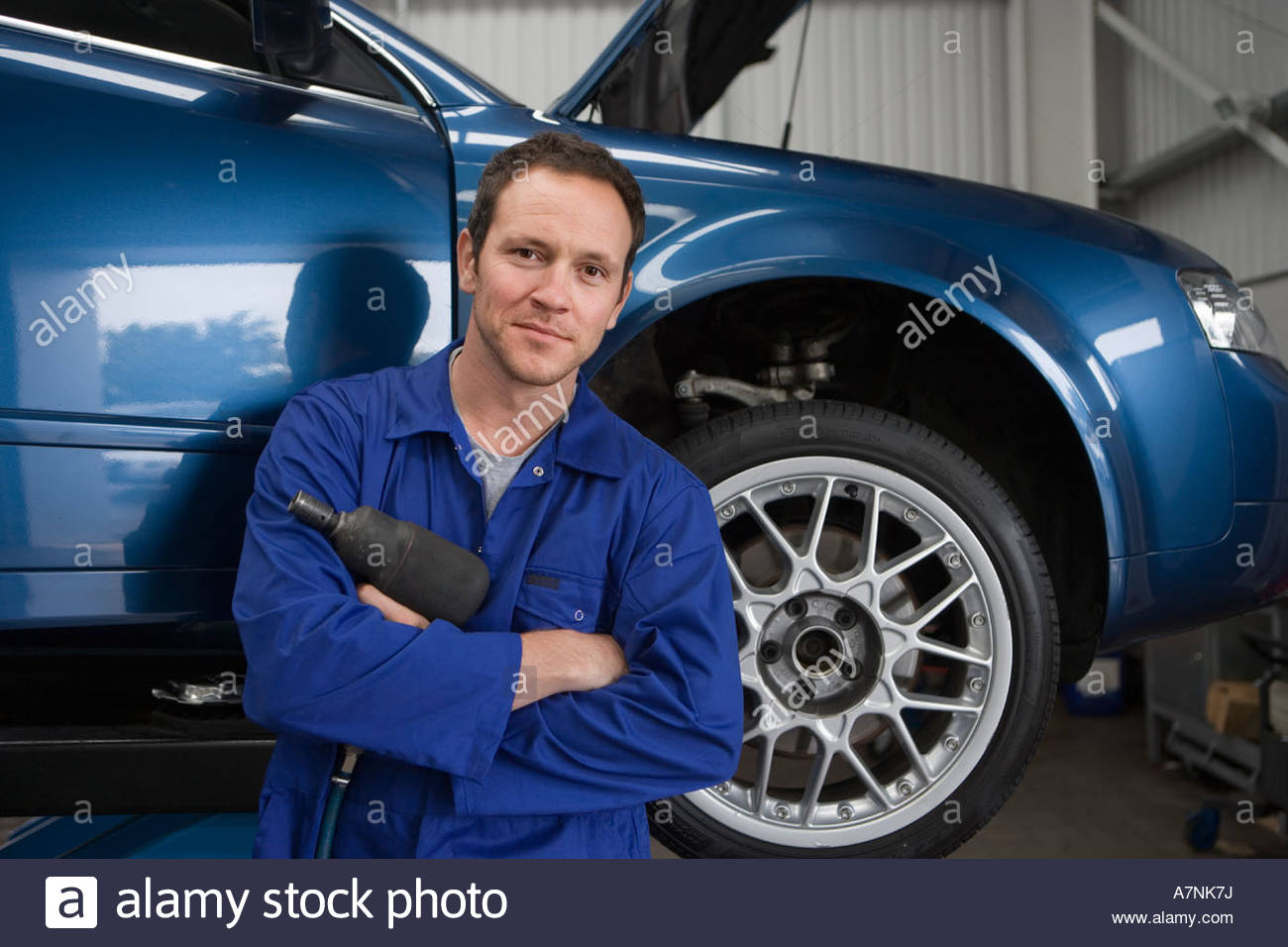 Male mechanic wearing blue overalls standing beside car on hydraulic platform in auto repair shop holding work tool - Stock Image