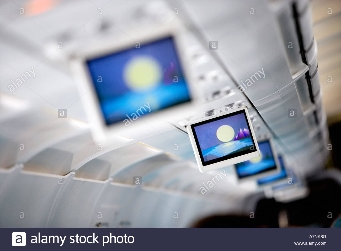 Row of blue visual screens in airplane cabin aisle differential focus - Stock Image