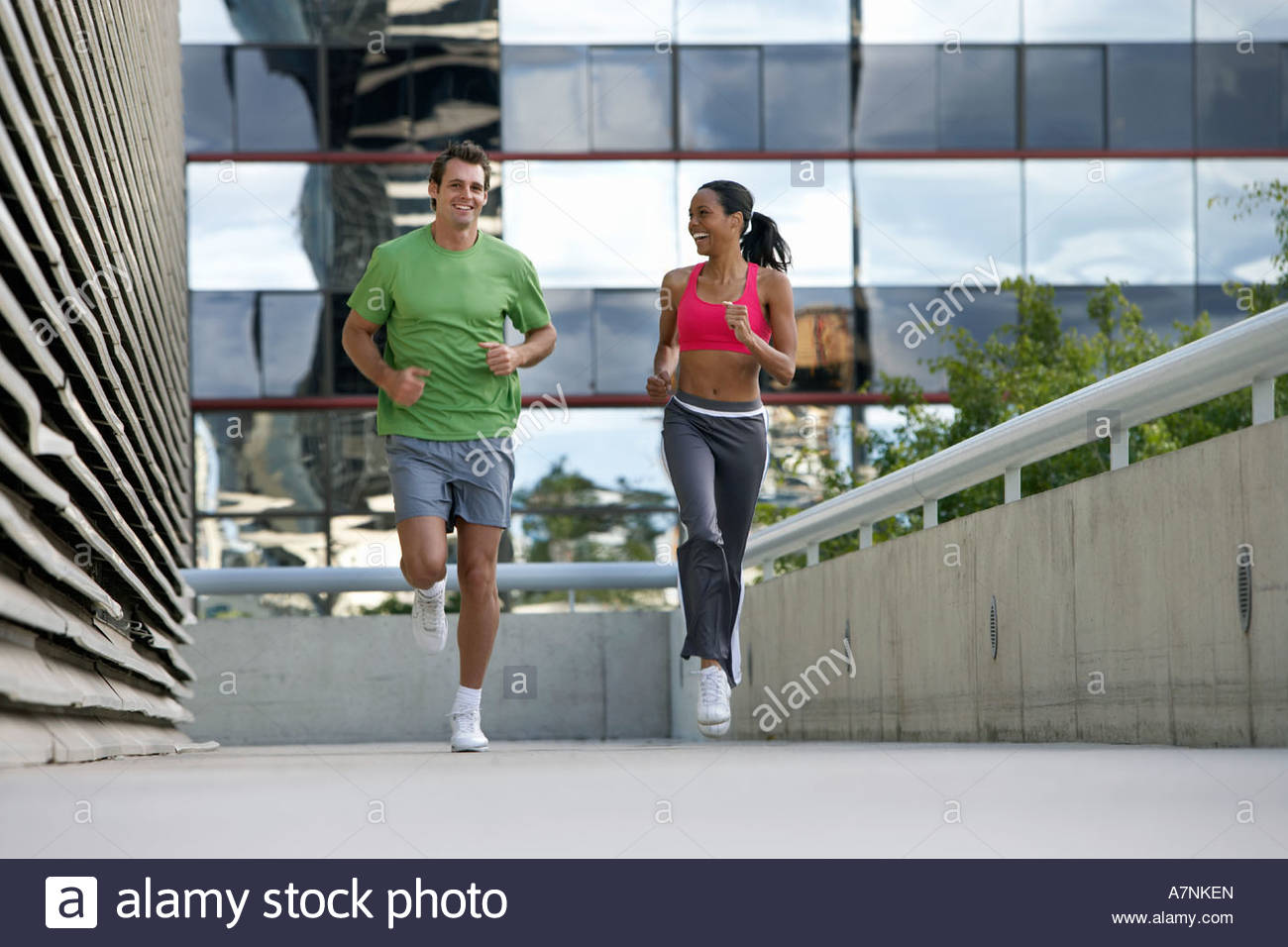 Couple jogging on urban elevated walkway running side by side smiling front view surface level - Stock Image