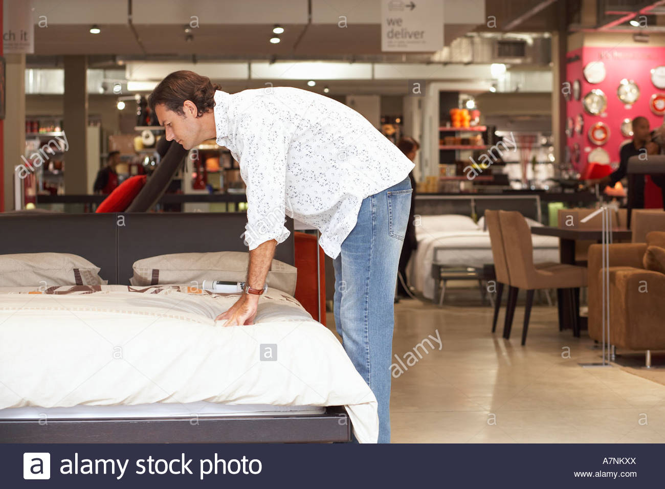 man testing mattress on new bed in furniture shop bending down side