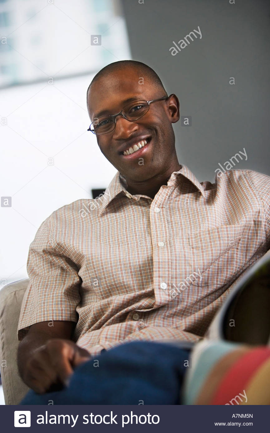 Man wearing spectacles and short sleeved shirt relaxing in chair at home smiling portrait tilt - Stock Image