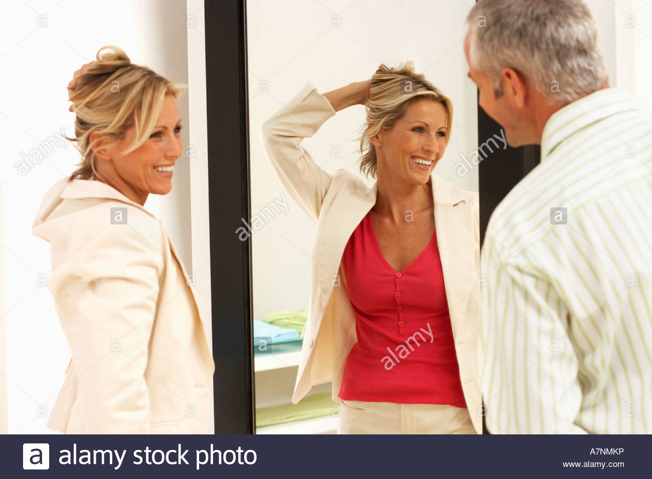 2fd84e4fa81e Woman trying on new clothes in fitting room hand in hair reflection in  mirror husband looking