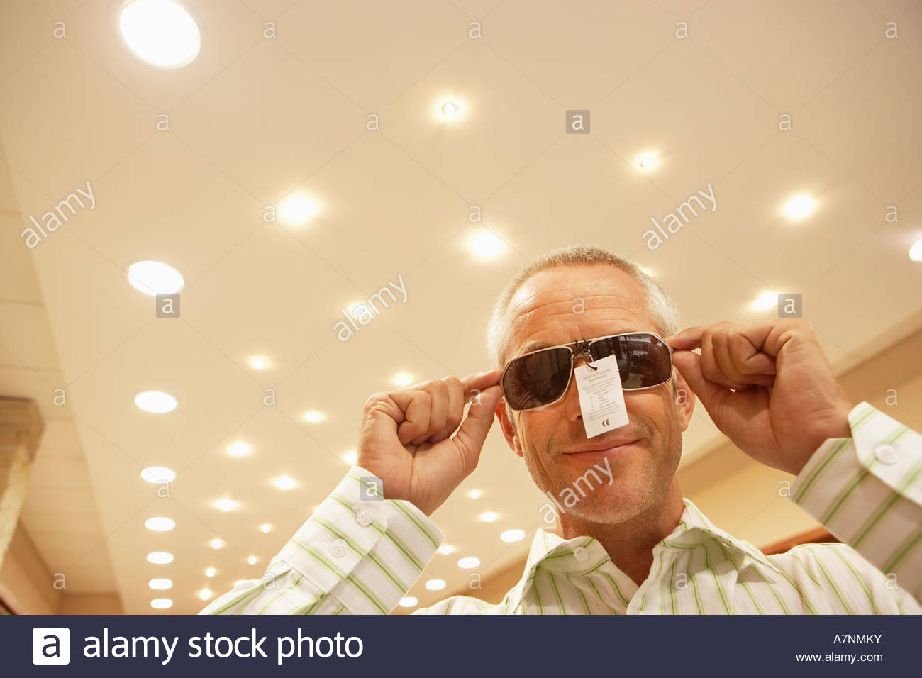 Mature man trying on pair of sunglasses in shop price tag attached smiling low angle view - Stock Image
