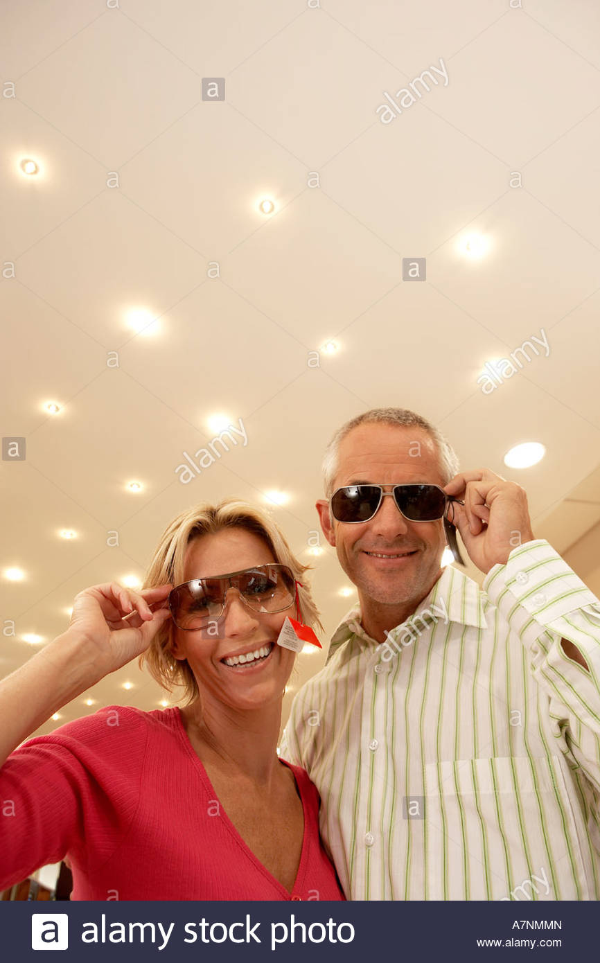 Mature couple trying on sunglasses in shop price tag attached smiling portrait low angle view - Stock Image