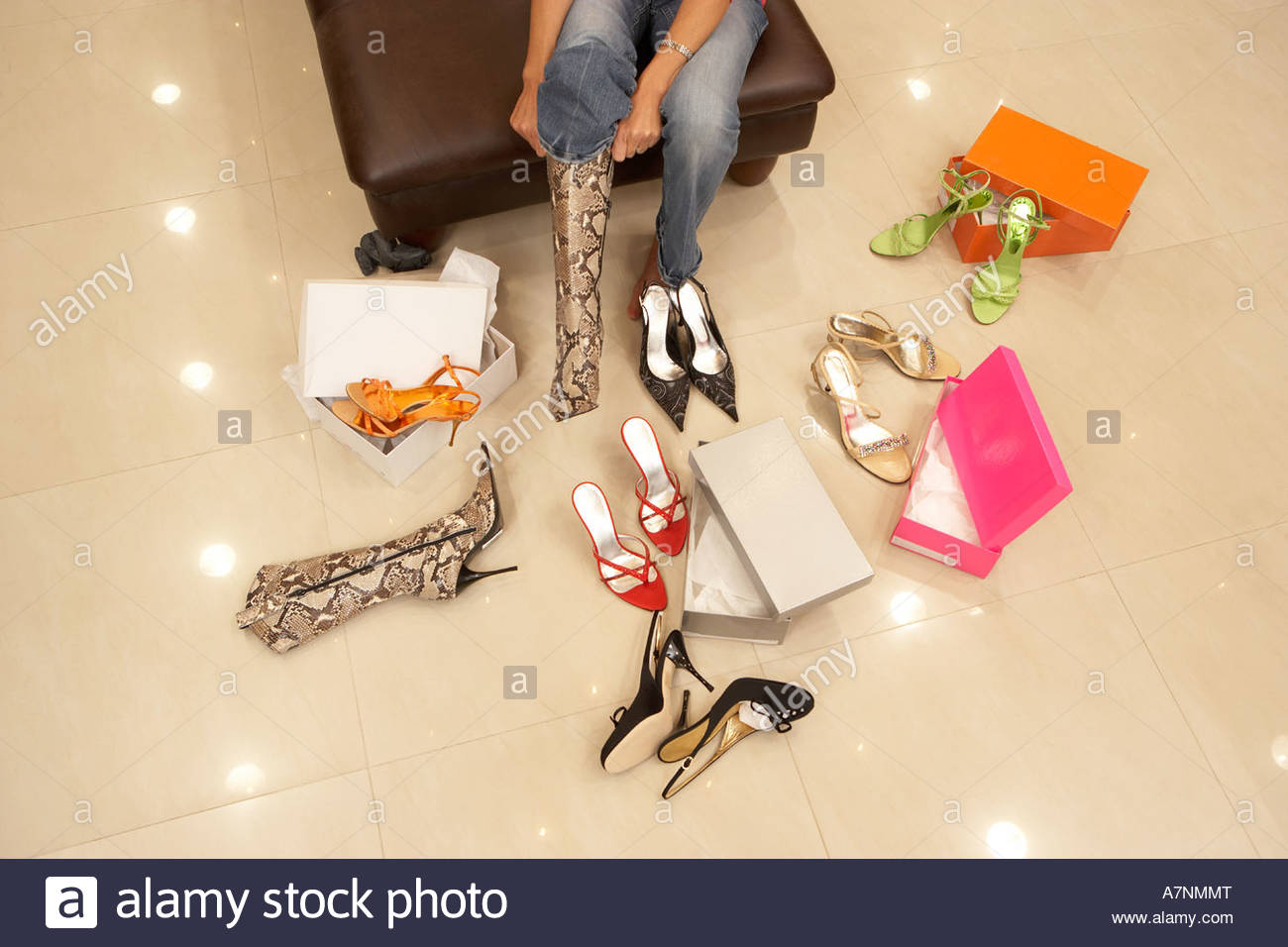 Woman trying on different pairs of high heels and boots in shoe shop low section elevated view - Stock Image