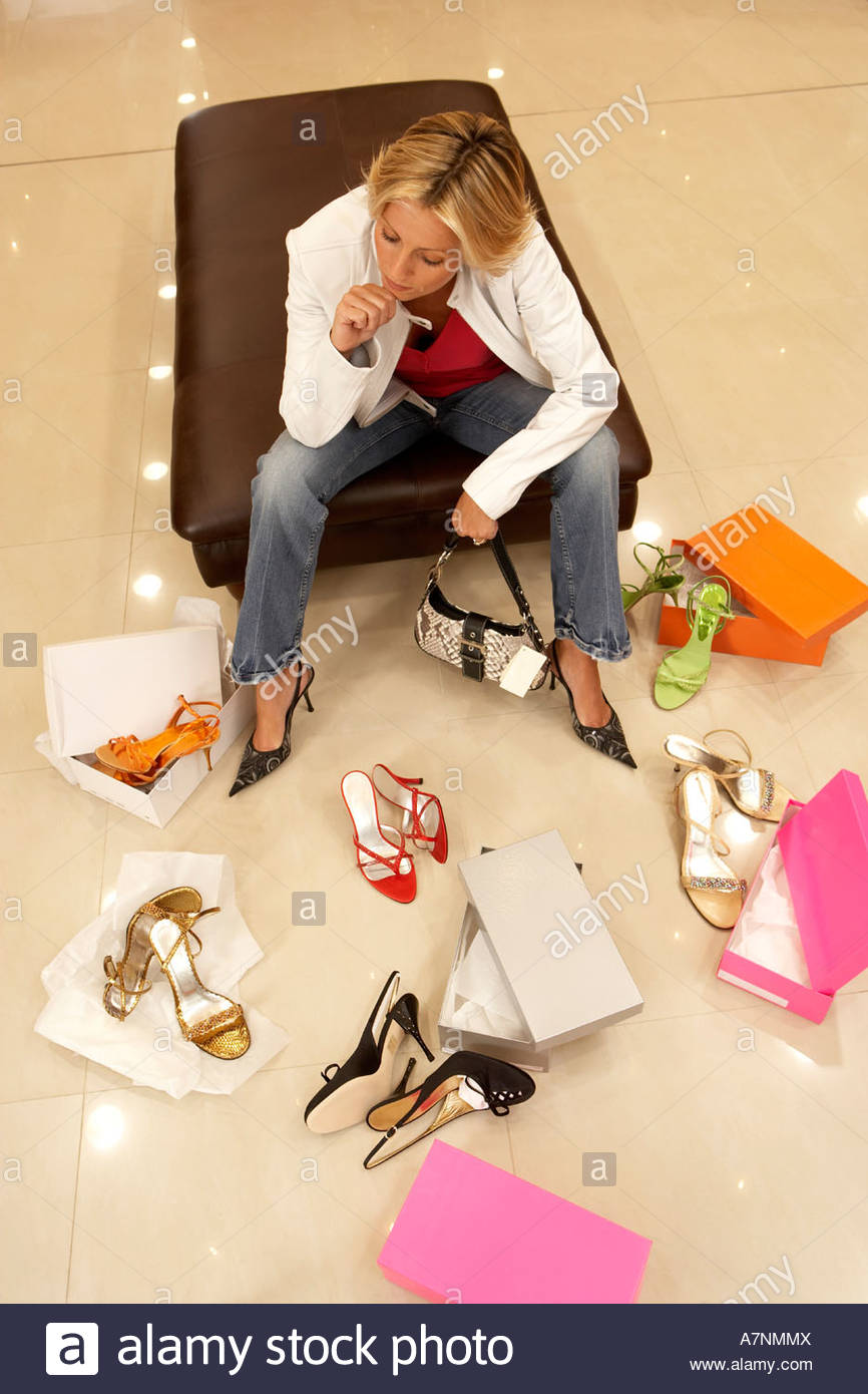 Mature blonde woman trying on different pairs of high heels in shoe shop hand on chin thinking elevated view - Stock Image