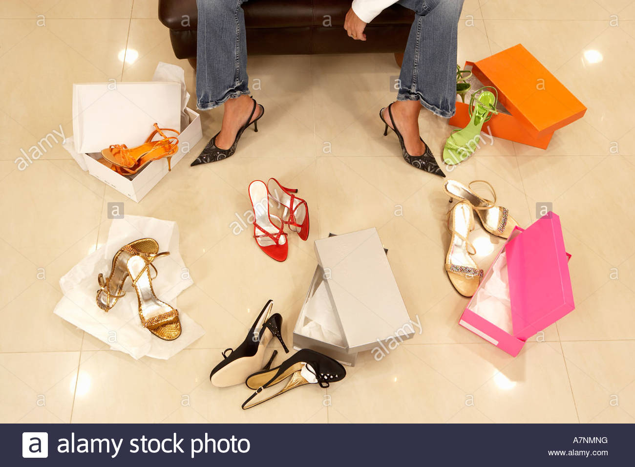 Woman trying on different pairs of high heels in shoe shop low section elevated view - Stock Image