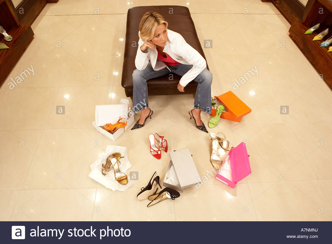 Mature blonde woman trying on different pairs of high heels in shoe shop thinking elevated view - Stock Image