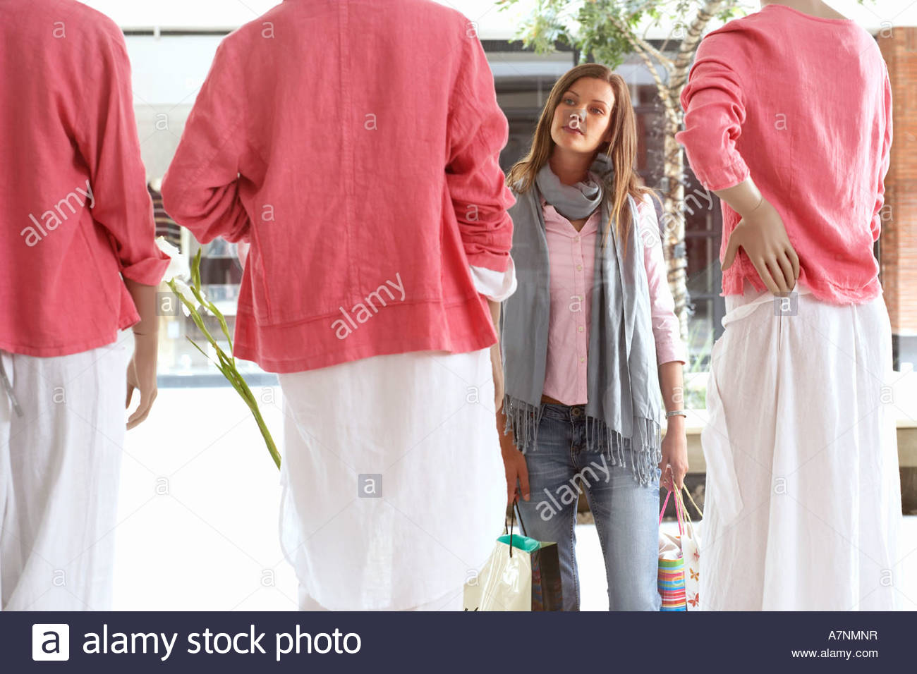 Woman window shopping looking at three mannequins wearing pink tops and white skirts in clothes shop - Stock Image