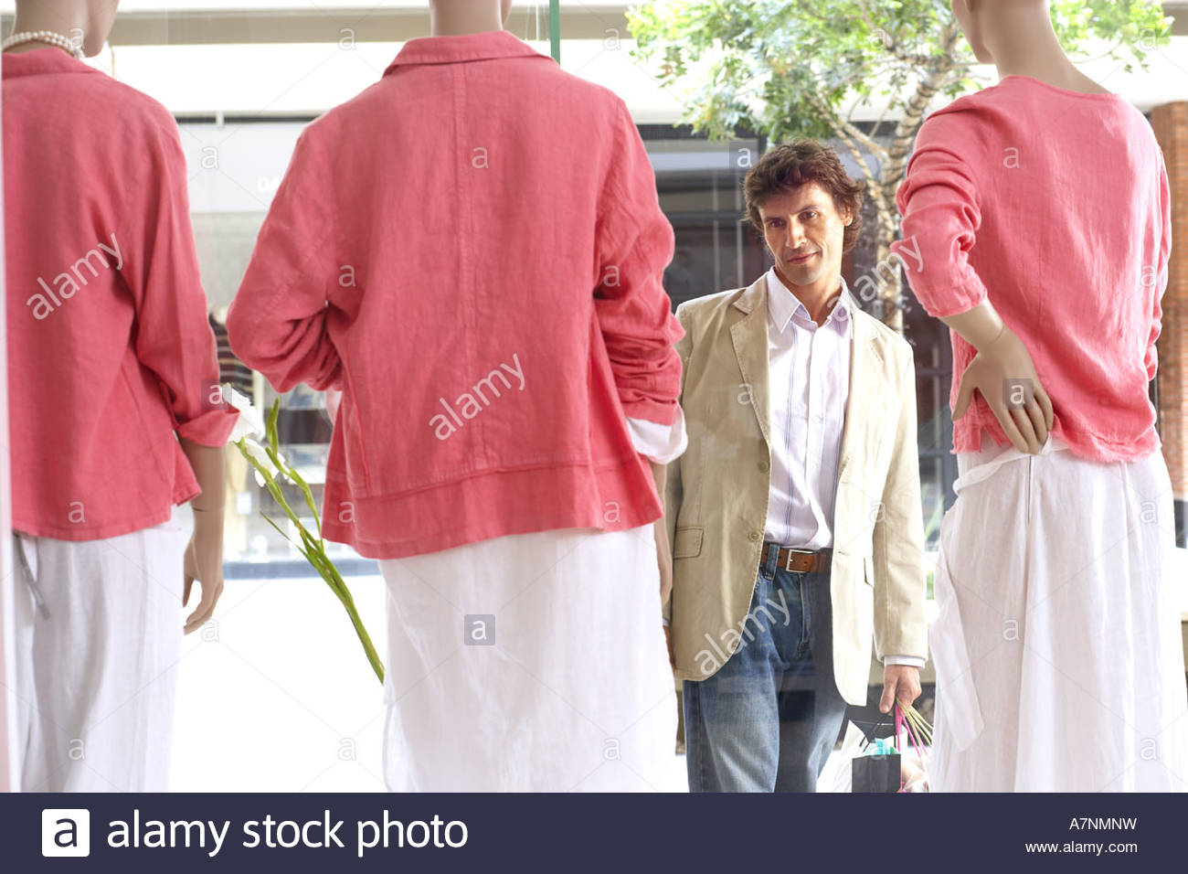 Man window shopping looking at three mannequins wearing pink tops and white skirts in clothes shop - Stock Image