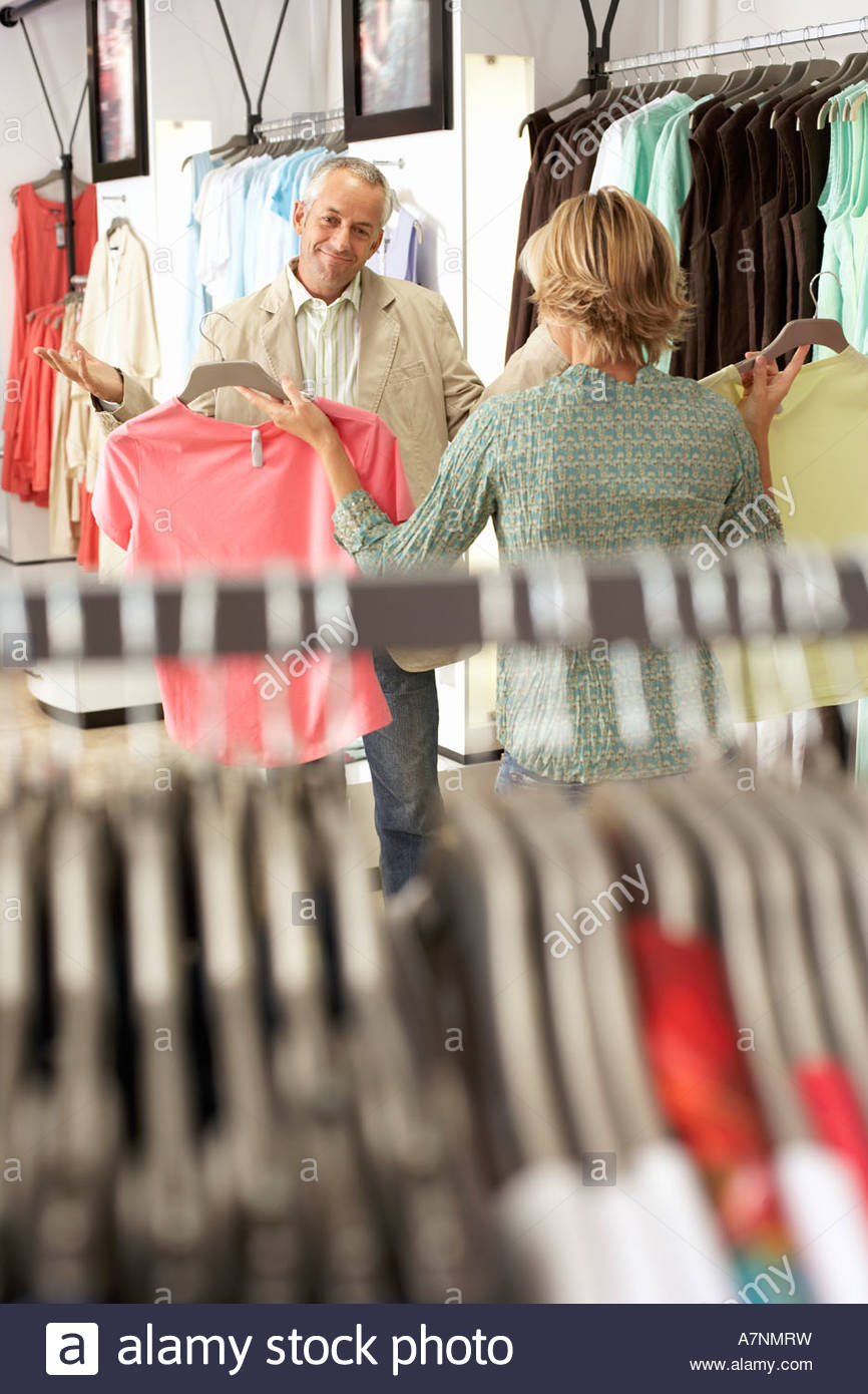 Mature couple shopping in clothes shop woman showing two different coloured tops to husband man shrugging shoulders - Stock Image