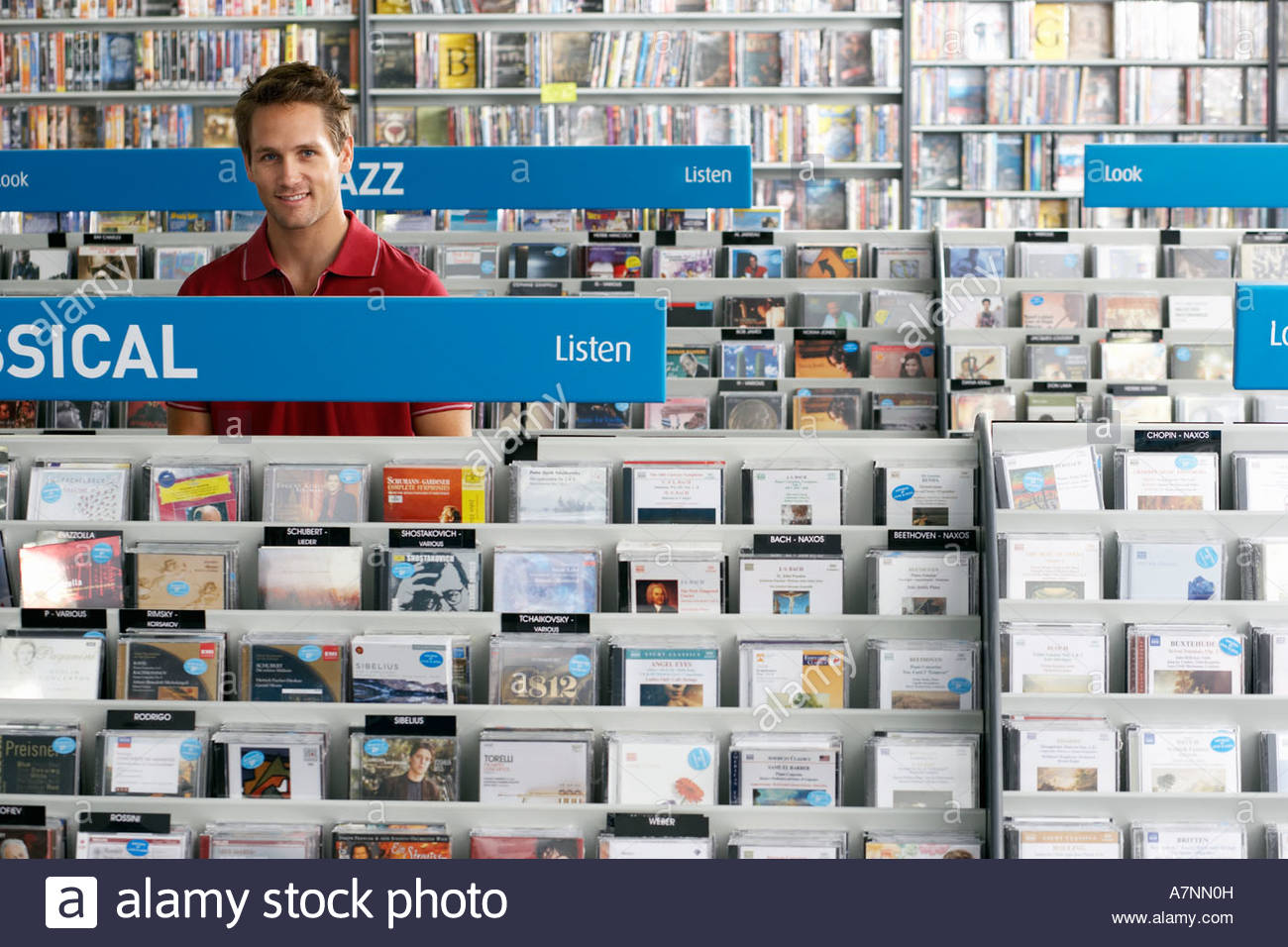 Man shopping for classical and jazz CDs in record shop standing in aisle behind rack smiling - Stock Image