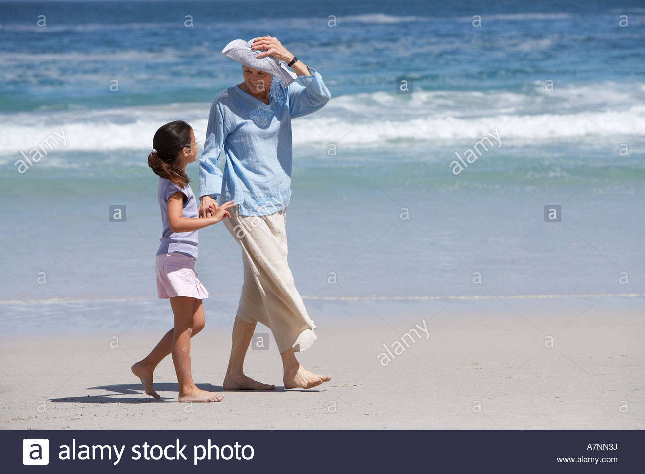 Mother and daughter 6 8 walking on beach holding hands woman holding sun hat in breeze smiling - Stock Image