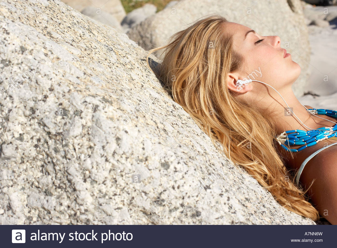 Blonde teenage girl 17 19 relaxing on beach leaning against rock eyes closed side view Stock Photo