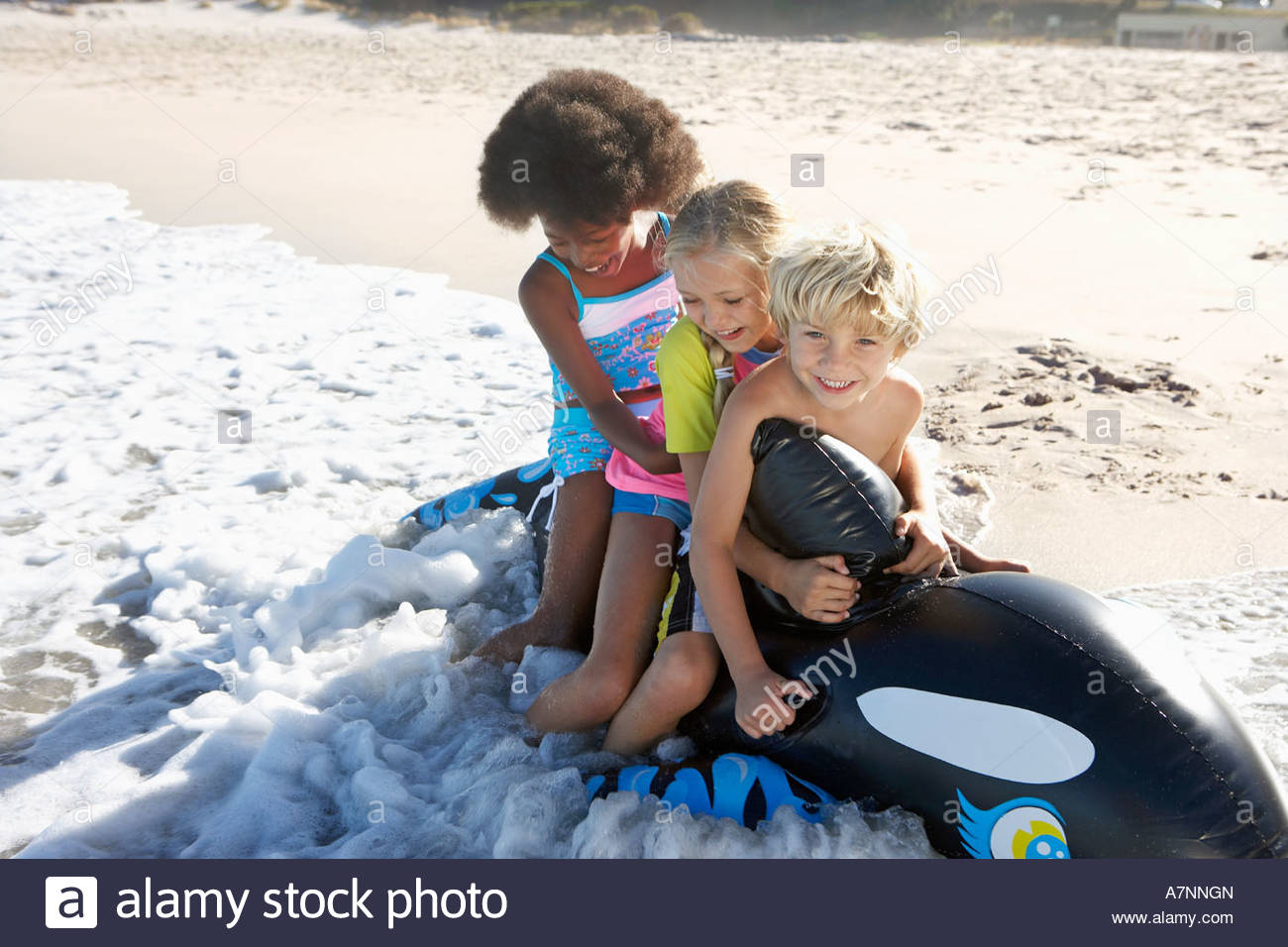 Three children 5 10 sitting on inflatable toy whale on beach playing in surf smiling - Stock Image