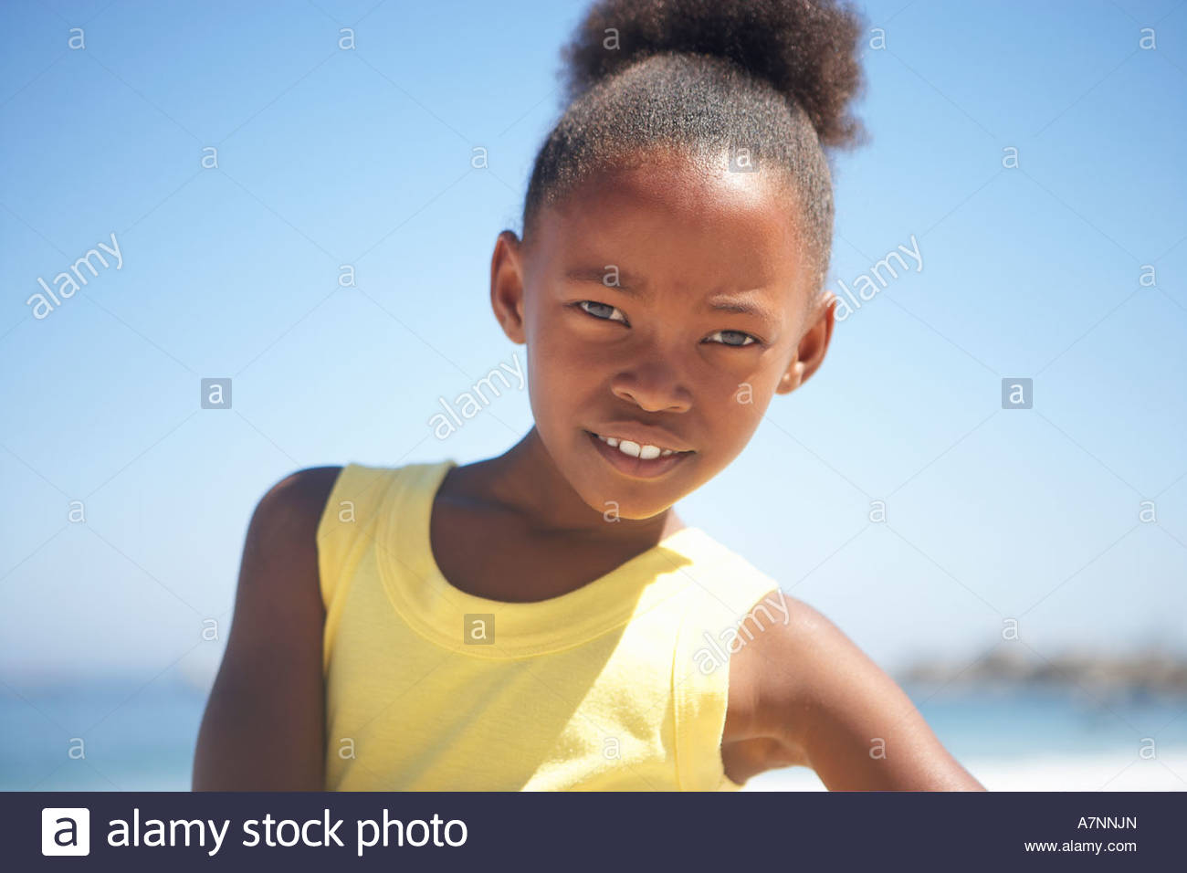 Girl 8 10 in yellow vest standing on beach smiling close up portrait - Stock Image