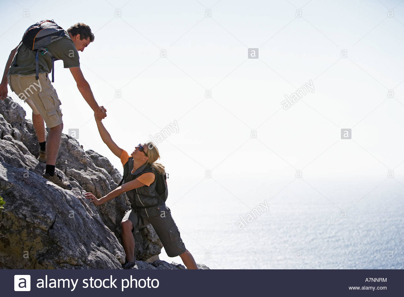 Couple climbing rock in bright sunlight man assisting woman side view sea in background - Stock Image